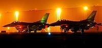 F-16 Fighting Falcons wait on the 'hot ramp' at a forward-deployed location while maintenance crews ready the weapons for a night mission  The F-16s a...