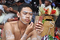 Denpasar (Bali, Indonesia): a Balinese adolescent putting on facial paintings at the Bali Arts Festival's opening