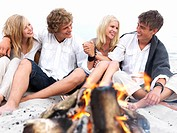 Happy young couples in casual sitting by bonfire at beach in summer