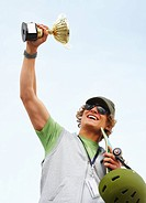 Happy handsome young man holding first prize gold cup Rasied into the sky