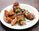 Meat, courgette and pepper kebabs with potato wedges