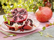 Pomegranate, cut into pieces, on plate beside whole fruit