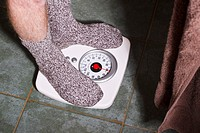 Man in socks weighing himself on a bathroom scale