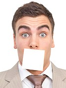 Portrait of a businessman with a blank white adhesive note over his mouth Shut up Isolated on white