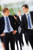 Motion blurred portrait of a business group, walking towards the viewer