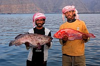 Two local Omani fishermen proudly present their catch, Musandam, Sultanate of Oman