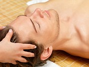 Close up portrait of a young man getting a facial massage on his holiday at the day spa