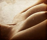 A beautiful pair of breasts with oil and water drops isolated on a white background A grunge texture added to the image to create the feel of a retro ...
