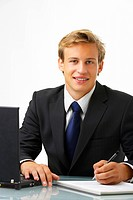 Business man working by desk _ Portrait of a handsome young man in a business suit working