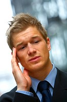 Worried Businessman with headache holding his forehead