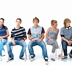 Young men and women sitting on chair in a line against white background