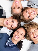 Closeup portrait of happy young friends lying on white floor