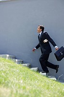 Businessman running up a stairway