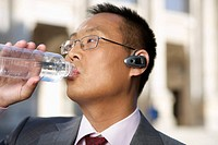 Businessman drinking water out of a plastic bottle