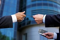One hand reaching a business card to another