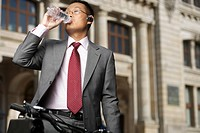 Businessman drinking water out of a plastic bottle (thumbnail)