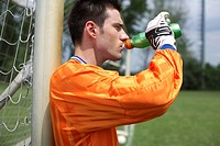 Goalkeeper leaning against goal while drinking