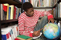 Student with earphones looking at a globe