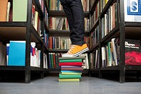 Person standing on stack of books between bookshelves