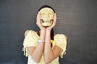 Young woman covering face with a skull