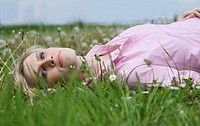 Young blond woman lying on meadow