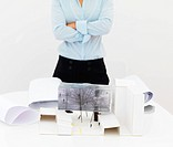 Midsection of a female architect standing against white background with a house model