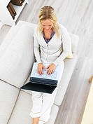 Top view of a young woman sitting on sofa and using laptop