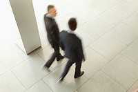 Two businessmen walking in lobby, Munich, Bavaria, Germany