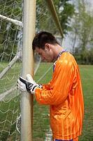Goalkeeper leaning against goal