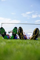 Two exhausted soccer players lying on grass