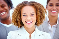 Closeup portrait of a smiling business woman standing with executives against white background