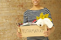 Woman carrying cardboard boxy with articles for flea market