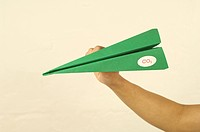Hand holding green paper plane with CO2 label