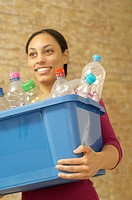 Woman carrying box with empty plastic bottles