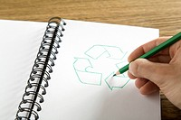Hand drawing recycling symbol in binder, Germany