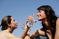 Two women drinking to close friendship with each other