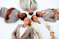 Happy business people lying down demonstrating unity