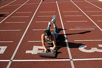 Woman lying with a laptop on a running track
