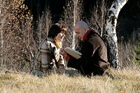 Man and woman sitting in front of a wood, reading in a book