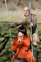 Mature man pushing woman on swing while she blowing her nose