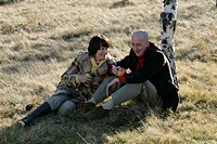 Mature couple sitting on grass and holding fruits in their hands