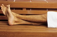Naked Legs of a Man with a Towel lying on a wooden Bench - Sauna - Relaxation - Wellness (thumbnail)