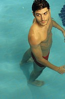 Darkhaired Man turns around while standing in Water _ Swimming Pool _ Look _ Leisure Time