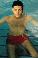 Darkhaired Man kneeling on the Stairs of a Swimming Pool _ Baths _ Leisure Time