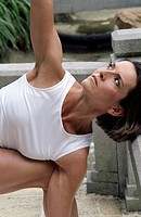 Darkhaired Woman stretching her Arm up - Physical Exercise - Yoga - Terrace (thumbnail)