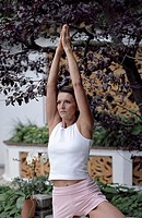 Darkhaired Woman lifting her Arms up _ Yoga _ Plants _ Garden