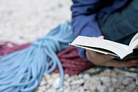 Young man with ropes lying next to him on the ground is reading a book part of, selective focus