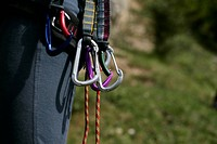 Person with carabiners fastened to a belt part of, selective focus