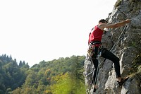 Young man climbing up a rocky wall, selective focus