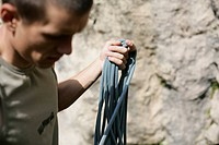 Young man in front of a rock face holding a climbing rope in his hand, selective focus